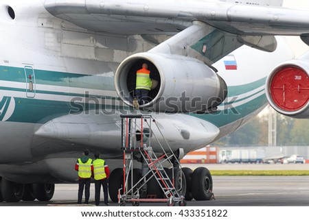 MOSCOW, RUSSIA - SEPTEMBER 26, 2014: Service Engineer serves a jet engine of the plane Il-76TD.