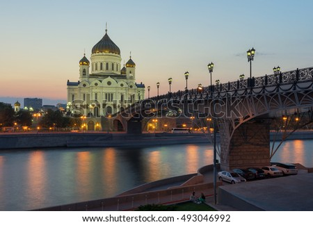 Moscow, Russia. The Cathedral Of Christ The Savior on the background of beautiful sunset. Patriarchy bridge unites the two banks of the Moscow river. Illumination accentuates the architectural idea.
