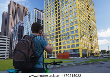 Moscow, Russia. The cyclist in old clothes calls on his cell phone and looks at the office centre. On the shoulders is wearing a backpack. Yellow house
