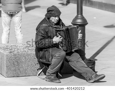 MOSCOW, RUSSIAN FEDERATION - APRIL 05: A street musician plays the accordion. Klimentovsky lane, on April 05, 2016 in Moscow, Russia. - stock photo