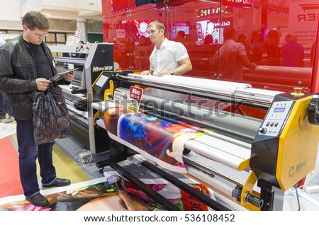 MOSCOW-SEPTEMBER 29, 2016: Business people are watching large format laminator brand Mefu at the International Trade Fair Advertising