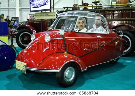 MOSCOW - SEPTEMBER 16: Men sit in a Messerschmitt KR 175 1953 at the international exhibition of the technical antiques on September 16, 2011 in Moscow, Russia - stock photo