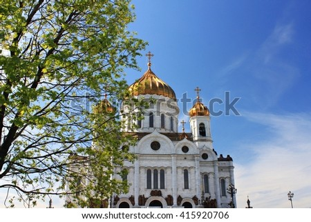 Moscow view in spring. Cathedral Christ the Saviour on sky background and fresh spring tree foliage. - stock photo