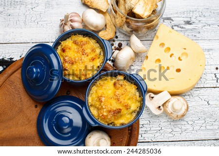 Moshroom casserole in a blue ceramic pot on wooden table - stock photo
