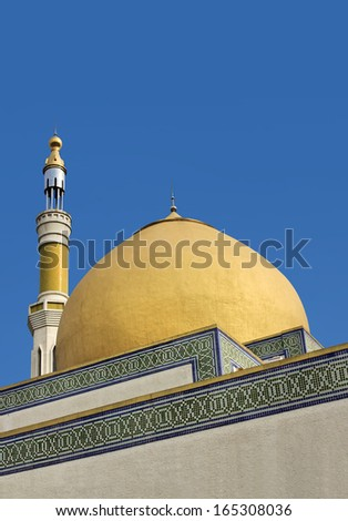 Mosque with golden dome and minaret - stock photo