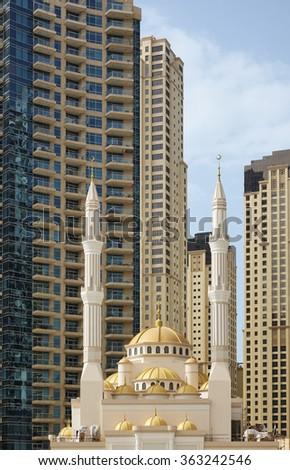 Mosque with highrise apartment buildings in Dubai, United Arab Emirates - stock photo