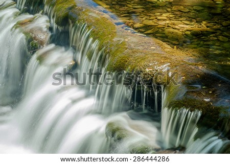 Moss covered smooth stones flowing over a shallow cascade and shallow clear clean water - stock photo