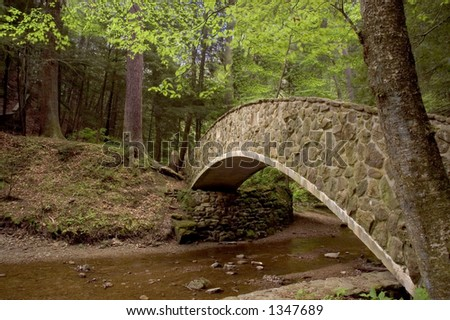 Moss covered stone bridge crossing a small stream. Located in Hocking Hills Ohio. - stock photo