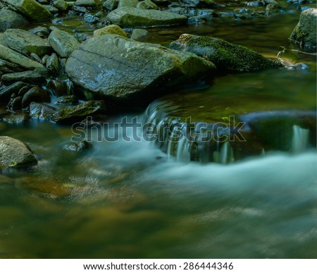 Moss covered stones in a shallow creek - stock photo
