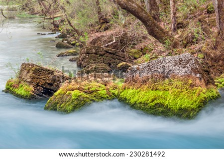 Mossy rocks along the banks of the flow from Big Spring in Missouri. - stock photo