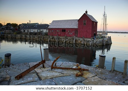 Most photographed famous fishing shack in Bearskin Neck Wharf in New England on the background with antique anchors on the foreground. - stock photo