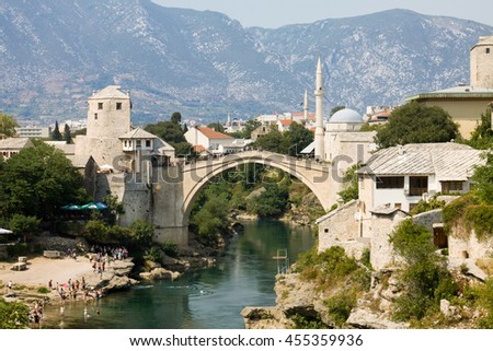 MOSTAR, BOSNIA AND HERZEGOVINA - AUGUST 25, 2012: Mostar cityscape with Neretva river and the Old Bridge. Mostar is a city in Bosnia and Herzegovina. The Old Bridge was built in the 16th century, - stock photo