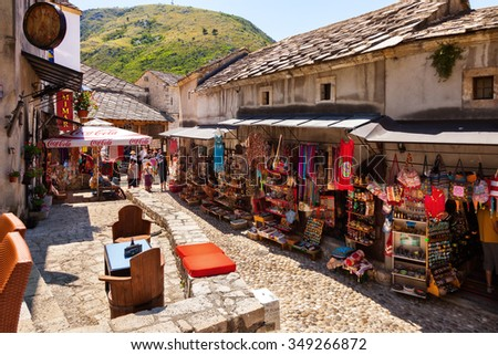 MOSTAR, BOSNIA AND HERZEGOVINA-JULY 20: People walking through the Old Town with many shops and cafes on July 20, 2014 in Mostar, Bosnia and Herzegovina. Mostar is situated on the Neretva River. - stock photo