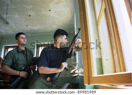 MOSTAR, BOSNIA, AUGUST 17: Bosnian Croat soldiers shoot at civilians from defensive positions in an apartment house during heavy fighting in Mostar, Bosnia, on August 17, 1993 - stock photo