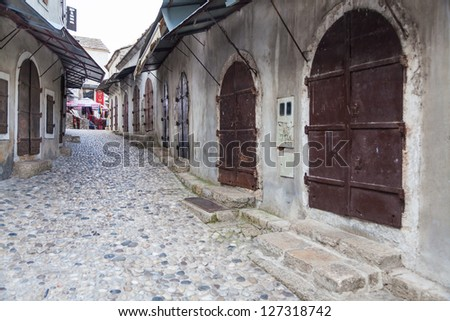 MOSTAR, BOSNIA - AUGUST 10, 2012: Pebble stone streets in old town on August 10, 2012 in Mostar, Bosnia. This old town founded in 1452, was mostly destroyed during the Bosnian war from 1991 to 1995. - stock photo