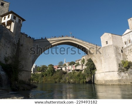 MOSTAR, BOSNIA, SEPTEMBER 30: a man is going to dive from the Old Bridge of Mostar. Arms outstretched, he is waiting for the money of the tourists to start, on september 30, 2014,  in Mostar, Bosnia. - stock photo
