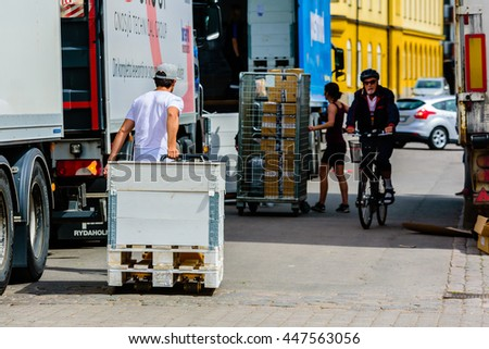Motala, Sweden - June 21, 2016: Young adult male using a pallet truck to transport a white wooden crate towards a truck for further transport. Real life situation.
