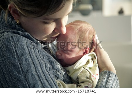Mother affectionately holding her newborn baby - stock photo