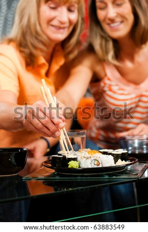 Mother and adult daughter eating sushi at home - FOCUS is on the hands