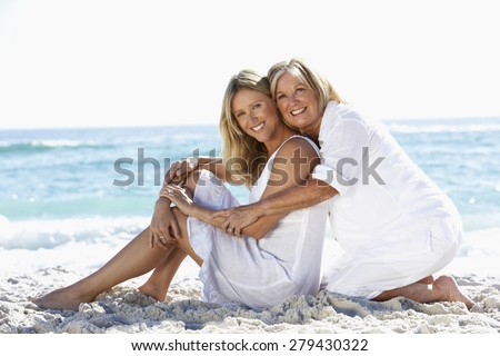 Mother And Adult Daughter Sitting Together On Beach - stock photo