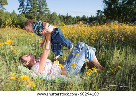 Mother and baby boy cuddling outdoors in flowers - stock photo