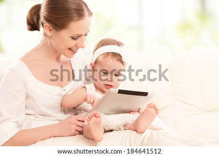 mother and baby child are looking to play and read tablet computer on the couch at home - stock photo