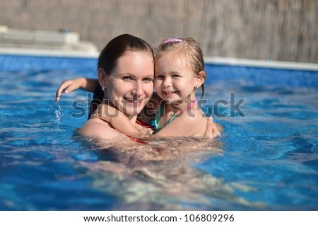 Mother and baby child playing in a swimming pool - stock photo