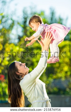 Mother and baby daughter are playing outdoors. Young mom and her cute little baby-girl are having fun in the sunny garden. Happy family childhood and motherhood concept.  - stock photo