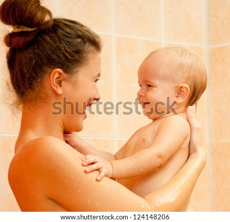 Mother and baby daughter in the shower - stock photo