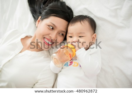 Mother and baby daughter plays, hugging, kissing at home on bed