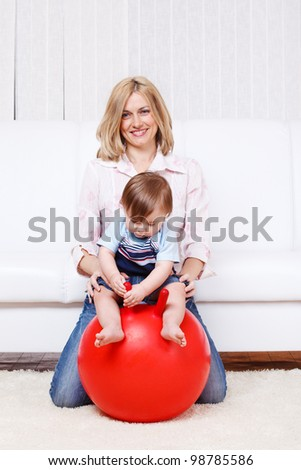 Mother and baby doing gymnastics on a large ball - stock photo