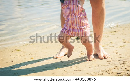 mother and baby feet at the beach sand. mom helps to make the child's first steps on the beach