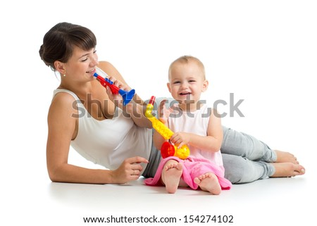 Mother and baby girl having fun with musical toys - stock photo