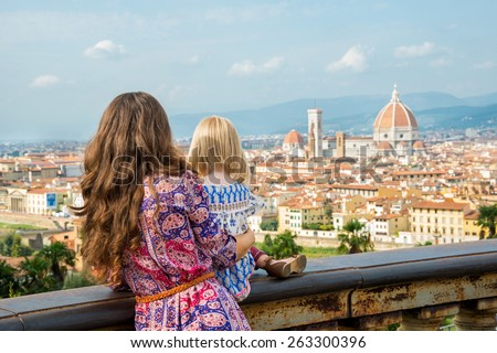 Mother and baby girl looking on panoramic view of florence, italy. rear view - stock photo