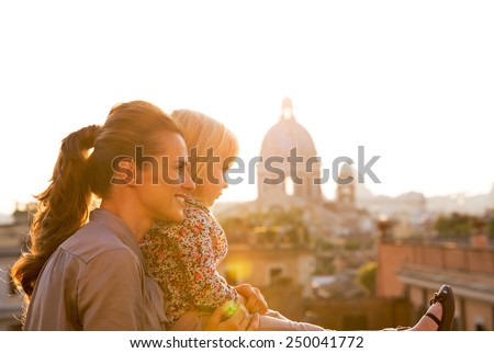Mother and baby girl looking on rome panorama on sunset - stock photo