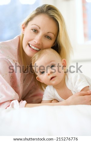 Mother and baby girl (9-12 months) smiling, portrait, close-up - stock photo