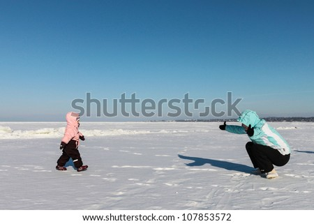 Mother and baby girl play on snow near the sea