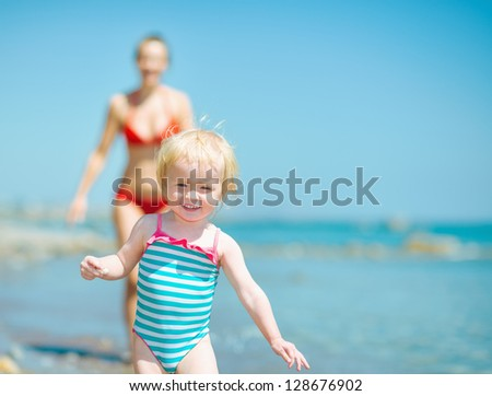 Mother and baby girl playing on sea shore - stock photo