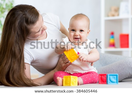 Mother and baby girl playing with color developmental toys in nursery - stock photo