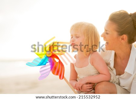 Mother and baby girl playing with colorful windmill toy on the beach in the evening - stock photo