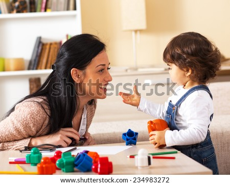 Mother and baby girl playing with toys in living room. - stock photo