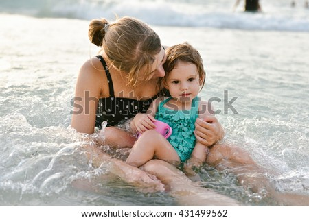 Mother and baby girl sitting in the water at the beach and enjoying their spare time.