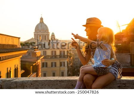 Mother and baby girl sitting on street overlooking rooftops of rome on sunset and pointing - stock photo