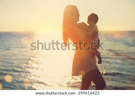 mother and baby having fun at sunset on the beach - stock photo