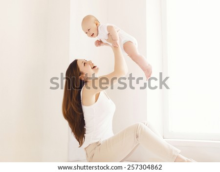 Mother and baby having fun together at home in white room, near window - stock photo