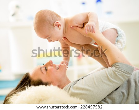 Mother and baby hugging and playing lying indoors - stock photo
