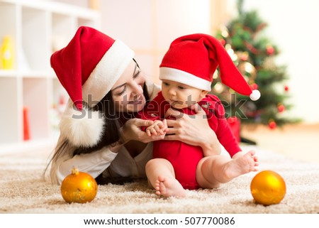 Mother and baby in santa red dress smile on a background of Christmas trees in the interior of the house