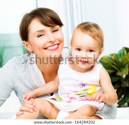 Mother and Baby kissing and hugging at Home. Mum and her Child - Little Daughter. Happy Smiling Family Portrait  - stock photo
