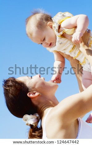 mother and baby on the beach - stock photo
