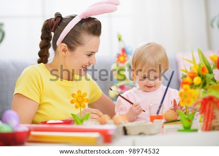Mother and baby painting on Easter eggs - stock photo
